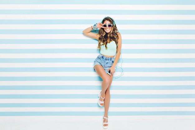 Look de verano brillante de alegre joven con pelo largo y rizado, gafas de sol, pantalones cortos con tacones divirtiéndose en la pared rayada. colores azules, expresando positividad, música, alegría, felicidad.