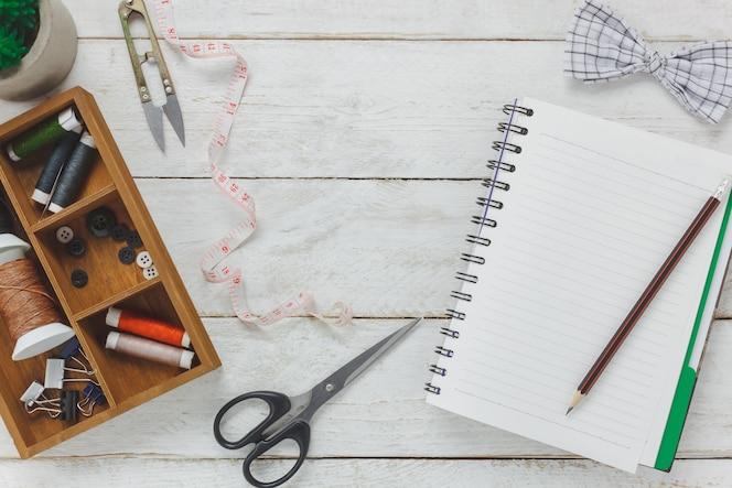 Los accesorios de la vista superior adaptan las herramientas del concepto.tailor está cortando las tijeras, la pajarita, los carretes del hilo de rosca, los botones y la ropa de costura. cuaderno de texto de espacio libre sobre fondo de madera rústica.