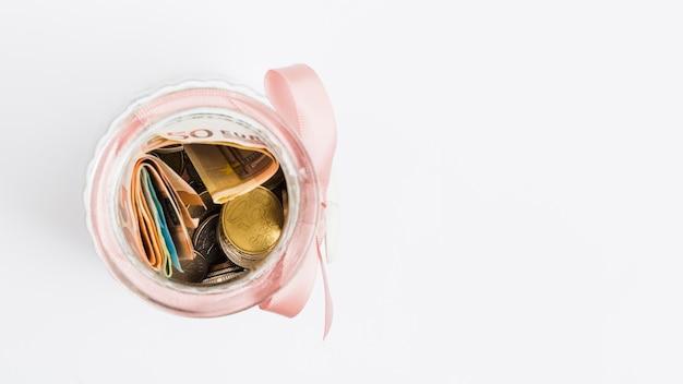 Los billetes y las monedas en el tarro de cristal atados con la cinta rosada en el fondo blanco