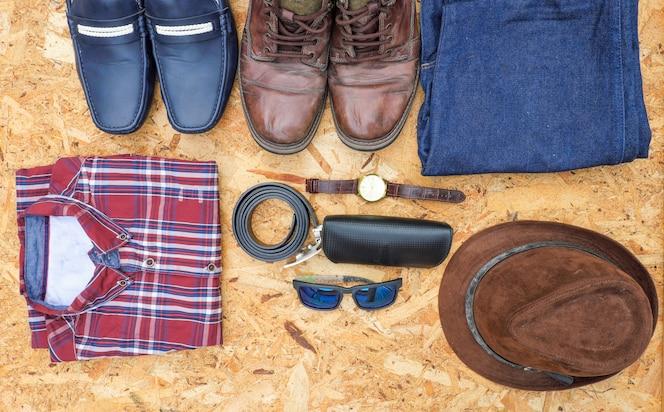 Los equipos casuales de los hombres con los accesorios de cuero en el fondo de madera, concepto de la moda.