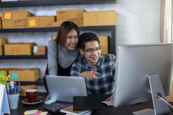 Los hombres de negocios asiáticos del dueño de la pareja trabajan en casa para las compras en línea, controlando la orden de