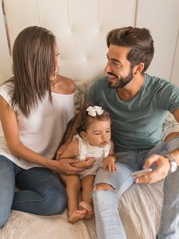 Los jóvenes con bebé y teléfono inteligente mirándose