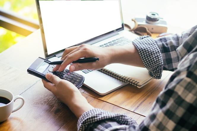 Los jóvenes empresarios utilizan calculadora de mano, portátil colocado en un escritorio junto a la ventana