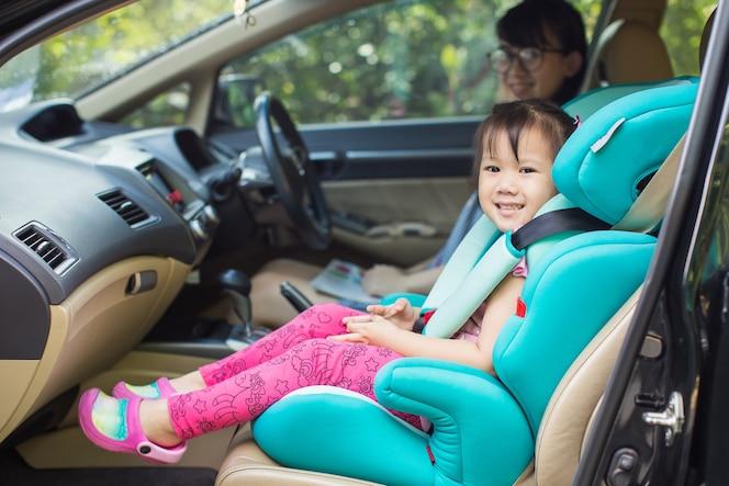 Los niños esperan a la madre y se sientan en el asiento del automóvil por seguridad antes de ir a la escuela.
