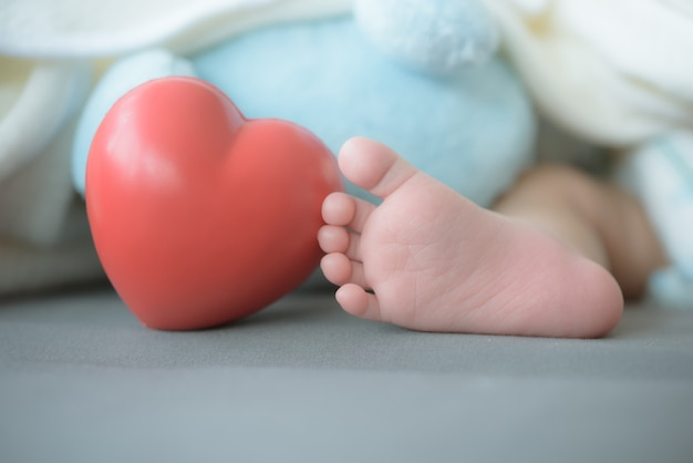 Los pies del bebé con un corazón rojo