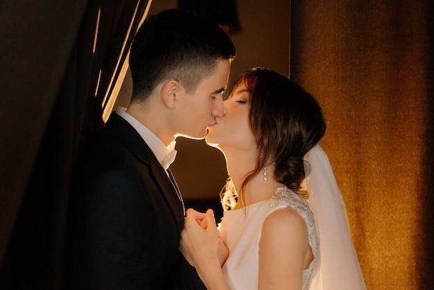 Lose¡retrato de besos de novios recién casados tomados de la mano en el día de la boda. boda, amor, concepto de relación. clave baja.