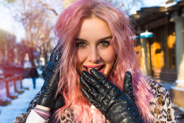 Ð¡lose up retrato de mujer bonita con pelos ondulados inusuales de color rosa, posando en la calle nevada en época de invierno, hermosos ojos, sonrisa y elegantes guantes de cuero con tachuelas, estilo rock.