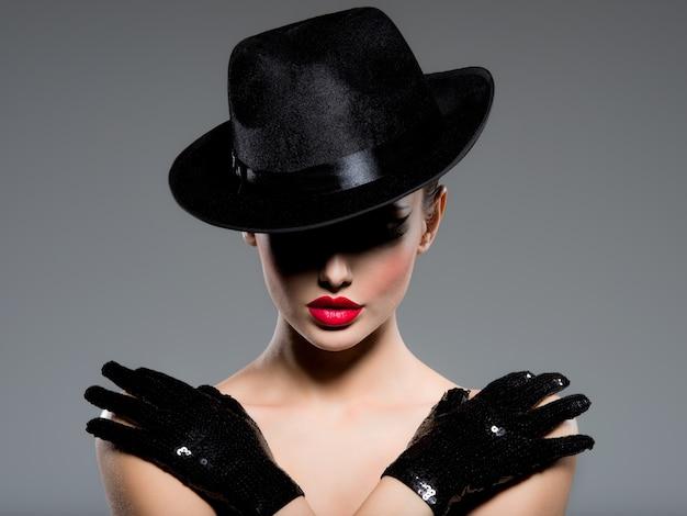 Сlose-up retrato de una mujer con un sombrero negro y guantes con labios rojos posando