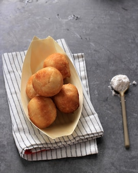 Loukoumades, luqaimat o lokma en placa sobre fondo de hormigón gris. loukoumades son donunts de cocina oriental populares durante ramazan. comida popular de ramadán. dulces iftar y suhur. copia espacio