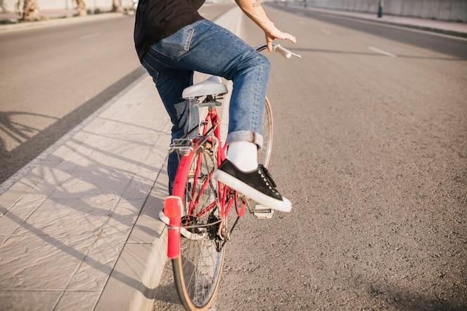 Lowsection del hombre sentado en bicicleta roja