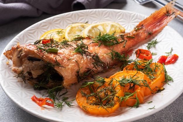 Lubina al horno con tomate pimiento limón y hierbas en un plato de cerámica sobre un gris