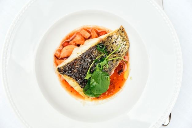 Lubina asada servida en un plato blanco rico en ácidos grasos saludables de pescado.