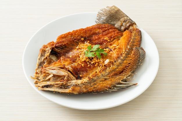 Lubina frita con ajo en plato