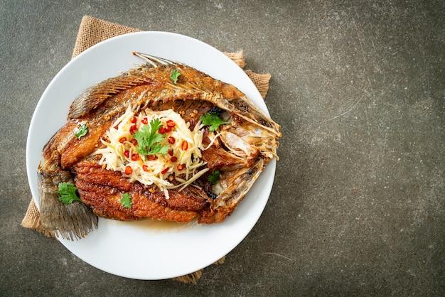 Lubina frita con salsa de pescado y ensalada picante en un plato