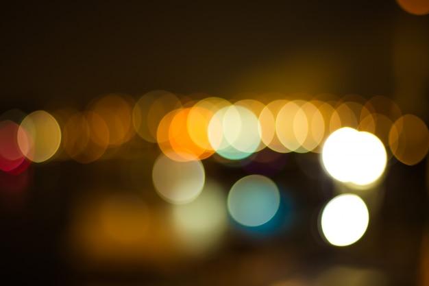 Luces abstractas del bokeh en la calle del camino en fondo ligero de la noche de la ciudad