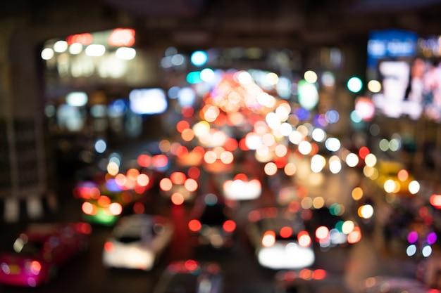 Las luces de bokeh del automóvil están en el medio de la carretera por la noche. la luz trasera del automóvil se refleja.