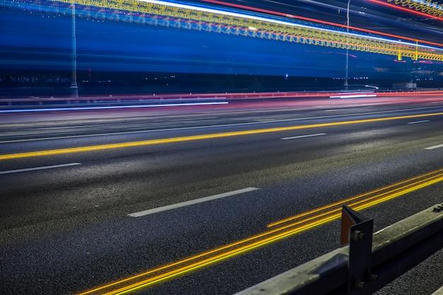 Luces de cola borrosas y semáforos en carretera