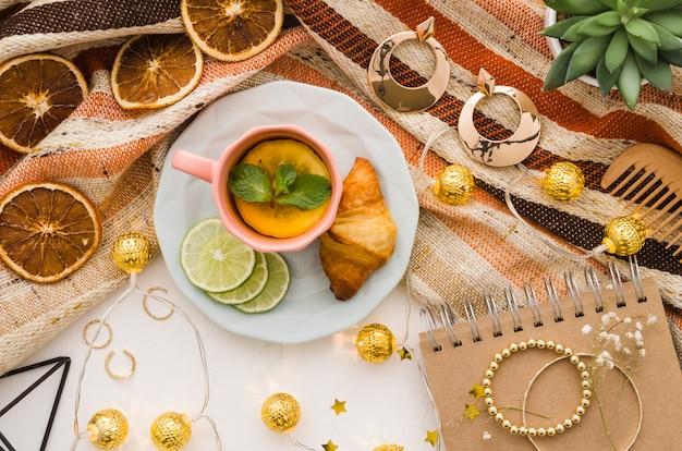 Luces decorativas doradas con accesorios femeninos y taza de té sobre fondo blanco