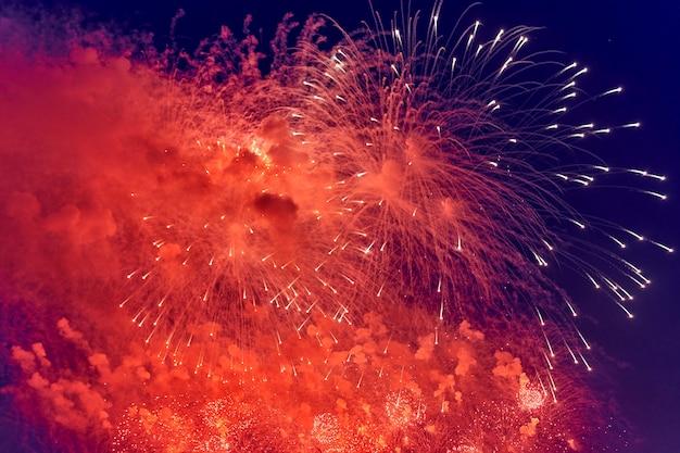 Luces de fuegos artificiales multicolores borrosas contra el cielo nocturno oscuro