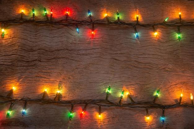 Luces de navidad sobre fondo de tablón de madera. feliz navidad y próspero año nuevo con espacio para copiar un texto.