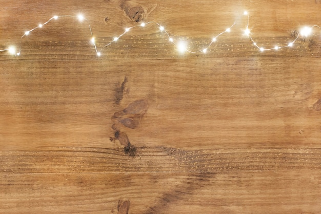 Luces de la navidad en tapa en fondo de madera.