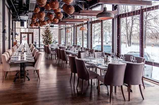 Luces navideñas, decoración, restaurante moderno interior, ventanas panorámicas, escenario, banquete, sillas de tela gris, mesas de servicio, copa de vino, platos, cubiertos. año nuevo festivo, invierno