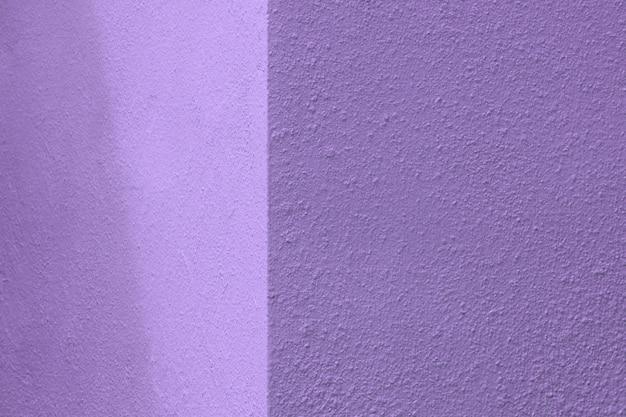 Luces y sombras en esquina de muro de hormigón morado.