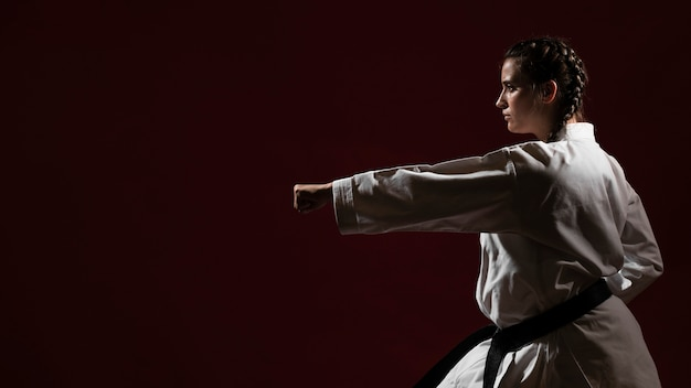 Lucha contra la mujer en uniforme de karate blanco y copia espacio