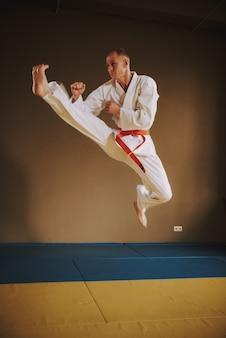 Luchador de artes marciales en blanco saltando con patada