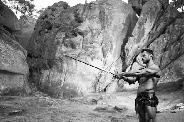 Luchador hábil. disparo monocromo de un guerrero con cuerpo musculoso fuerte señalando su espada de pie cerca de la roca copyspace