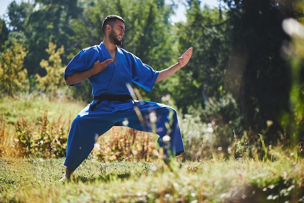 Luchador de karate kazajo asiático es combate en kimono azul uniforme en un hermoso paisaje de verano con espacio de copia