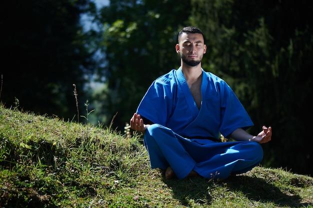 Luchador de karate kazajo asiático es meditar en kimono azul uniforme en un hermoso paisaje de verano