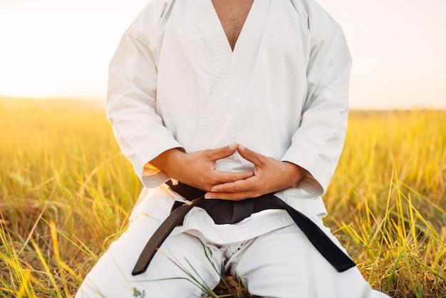 Luchador de karate masculino sentado en el suelo en el campo