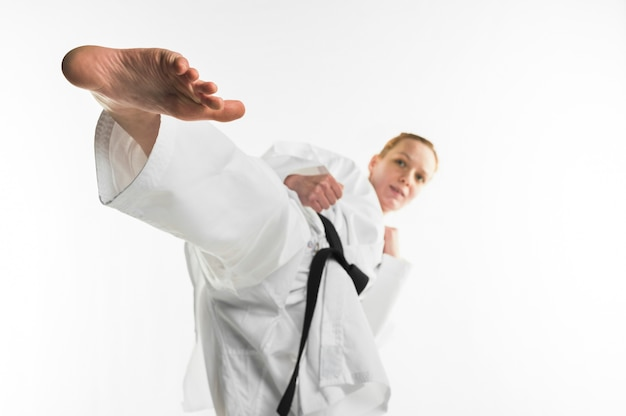 Luchador de karate pateando con el pie