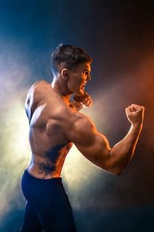 Luchador muscular perforando en humo. color de fondo.