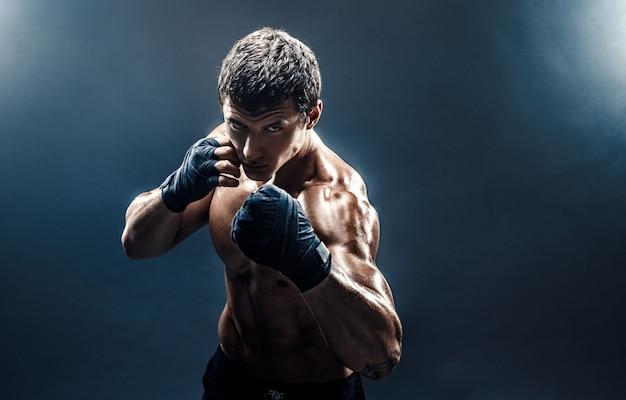 Luchador musculoso en topless en guantes de boxeo