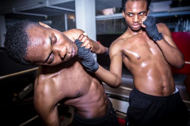 Luchador rápido afroamericano que golpea en la barbilla a su oponente.