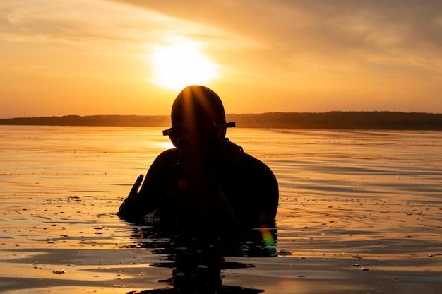 Luchador de una unidad especial sale del agua y se prepara para el inicio de la operación. técnica mixta. el concepto de inestabilidad en el mundo, hostilidades, crisis. rusia vs estados unidos