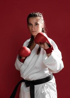Luchadora con guantes de box sobre fondo rojo.