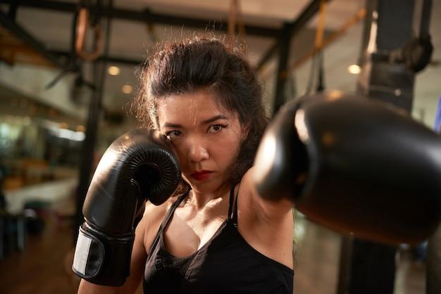 Luchadora haciendo un gesto de golpe hacia la cámara con sus guantes de boxeo