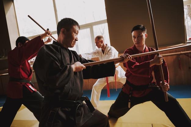 Luchadores de artes marciales luchando con palos en el gimnasio.