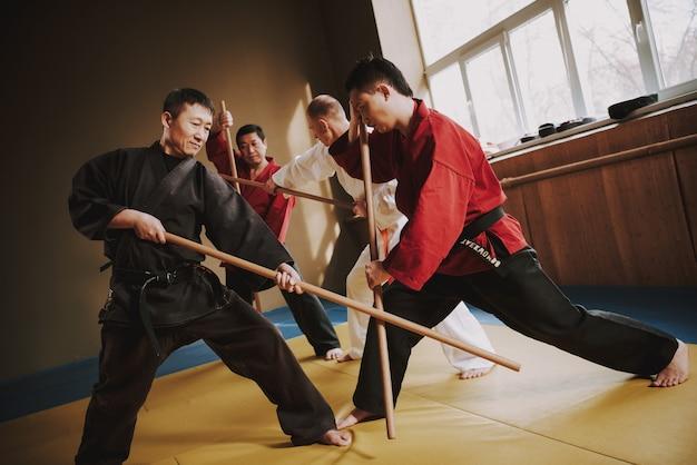 Luchadores de artes marciales luchando con palos.