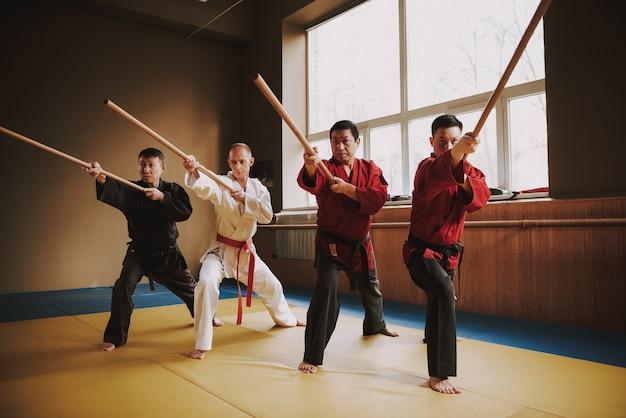 Luchadores de diferentes colores entrenando keikogi con palos.
