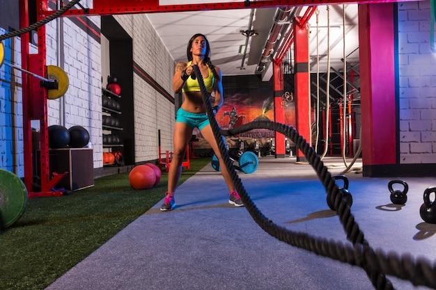 Luchando contra cuerdas chica en el ejercicio de entrenamiento de gimnasio