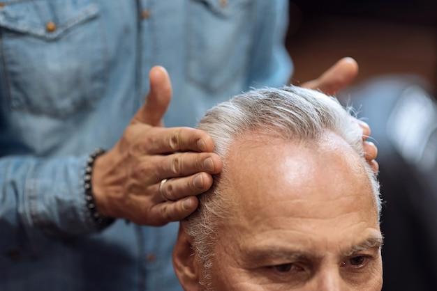 Luciendo bien. cerca del estilista masculino tocando las sienes de los clientes mayores mientras usa gel especial para el cabello.