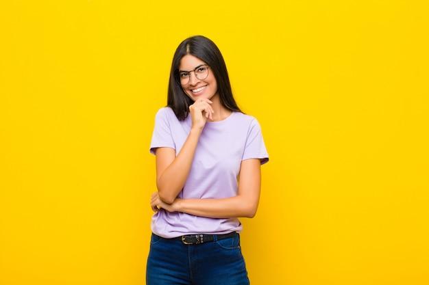 Luciendo feliz y sonriente con la mano en la barbilla, preguntándose o haciendo una pregunta, comparando opciones