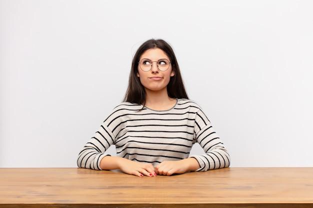 Luciendo perplejo y confundido, preguntándose o tratando de resolver un problema o pensando
