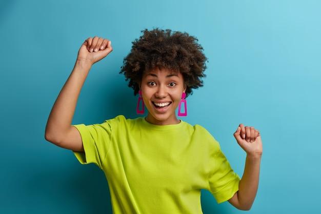 Lucky complacida joven de pelo rizado baila con las manos en alto, se divierte y expresa emociones positivas, libertad y felicidad, se siente como campeona, vestida con una camiseta verde brillante, ganó su objetivo