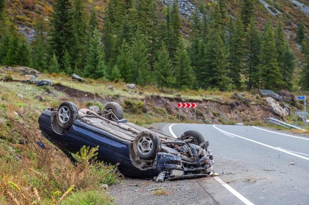 Lugar del accidente de coche en una curva, el coche volcado se encuentra en el techo,