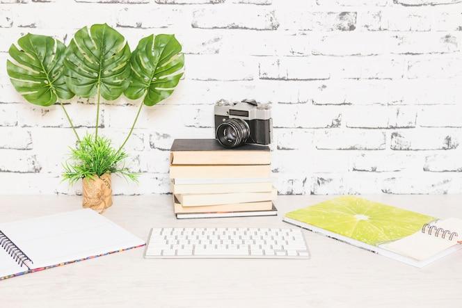 Lugar de trabajo creativo con libros y cámara